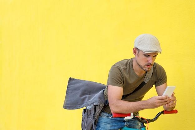 Vista laterale di un giovane uomo adulto con una bici d'epoca