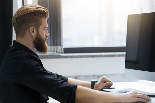 Vista laterale di un giovane uomo barbuto seduto alla sua scrivania