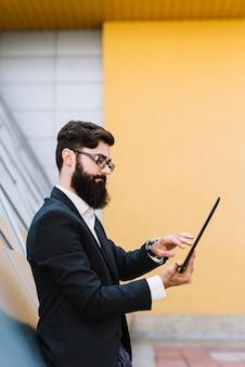 Vista laterale di un giovane uomo d'affari che utilizza compressa digitale che sta contro la parete