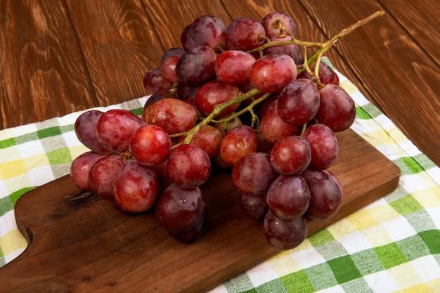 Vista laterale di un grappolo d'uva su una tavola di legno sul tavolo rustico