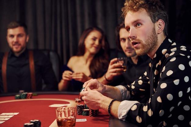 Vista laterale di un gruppo di giovani eleganti che giocano a poker nel casinò insieme