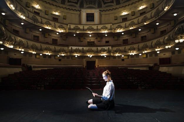 Vista laterale di un manoscritto della lettura del mimo femminile in auditorium vuoto