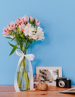Vista laterale di un mazzo di fiori di colore bianco e rosa alstroemeria in un vaso di vetro con foto incorniciata vecchia macchina fotografica e matassa di corda su un tavolo di legno su sfondo blu muro