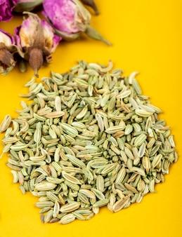 Vista laterale di un mucchio di semi di anice essiccati con boccioli di rosa tea su sfondo giallo