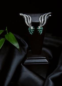 Vista laterale di un paio di orecchini in argento con diamanti e smeraldi su parete nera su fondo nero