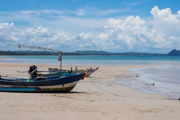 Vista laterale di un peschereccio di legno sulla spiaggia tropicale con sabbia e cielo blu bianchi