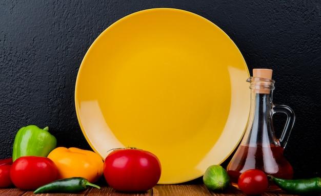 Vista laterale di un piatto giallo vuoto e pomodori freschi dei peperoni dolci degli ortaggi freschi e una bottiglia di olio d'oliva a buio