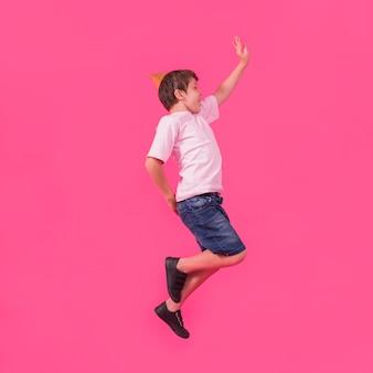Vista laterale di un ragazzo in cappello partito saltando su sfondo rosa