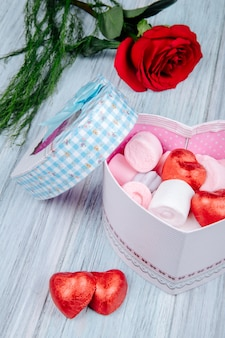 Vista laterale di un regalo a forma di cuore riempito con marshmallow rosa e caramelle al cioccolato avvolto in un foglio rosso e fiore di rosa rossa sul tavolo di legno grigio