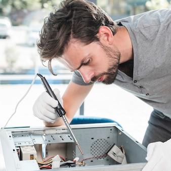 Vista laterale di un tecnico maschio che ripara il cpu del computer in officina