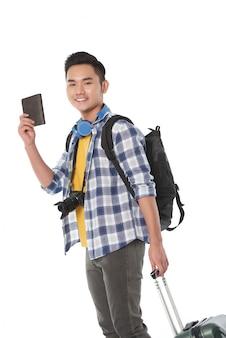 Vista laterale di un turista con bagaglio a mano pronto a presentare il suo passaporto