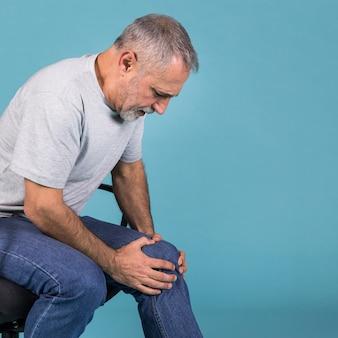 Vista laterale di un uomo anziano con dolore al ginocchio che si siede sulla sedia