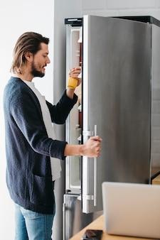 Vista laterale di un uomo che guarda la bottiglia di succo preso dal frigorifero a casa