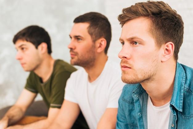 Vista laterale di un uomo che guarda la televisione con i loro amici