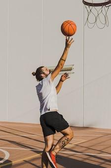 Vista laterale di un uomo che lancia la pallacanestro nel cerchio