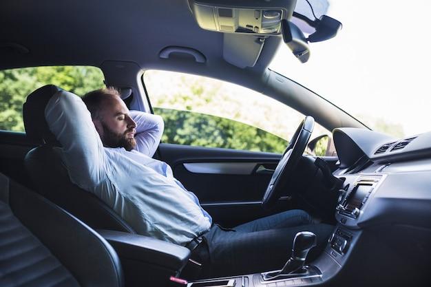Vista laterale di un uomo che si distende in auto