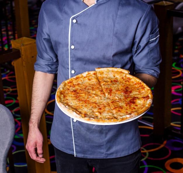 Vista laterale di un uomo che tiene la pizza al formaggio al caffè