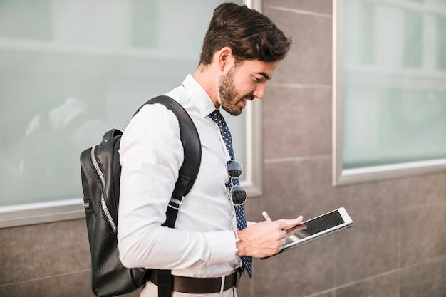 Vista laterale di un uomo che utilizza la tavoletta digitale