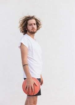 Vista laterale di un uomo con pallacanestro in piedi su sfondo bianco