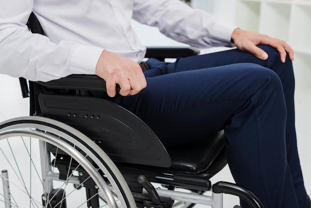 Vista laterale di un uomo d'affari che si siede sulla sedia a rotelle