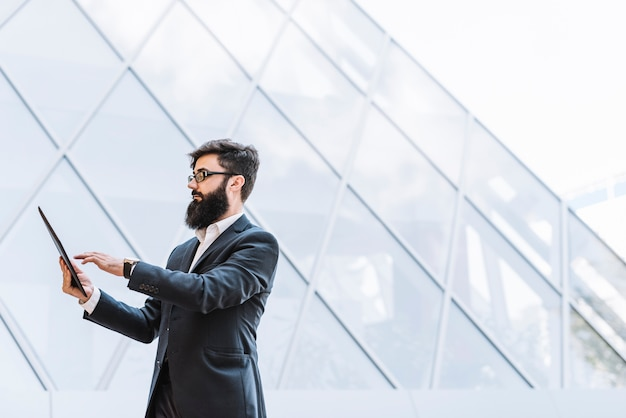 Vista laterale di un uomo d'affari con la barba lunga che utilizza compressa digitale che sta contro la costruzione di vetro