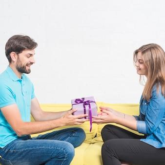 Vista laterale di un uomo felice che si siede sul divano dando il regalo di san valentino alla sua ragazza