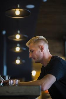 Vista laterale di un uomo seduto al bancone del bar
