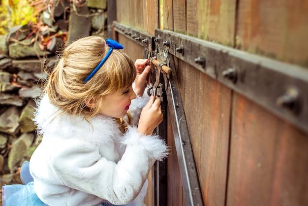 Vista laterale di una bella bambina nello scenario guardando nel buco della serratura del cancello