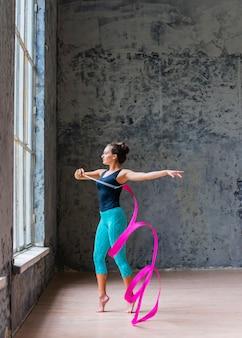 Vista laterale di una bella giovane donna che balla con nastro rosa
