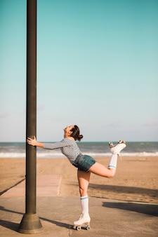 Vista laterale di una colonna della holding del pattinatore femminile che si leva in piedi davanti alla spiaggia