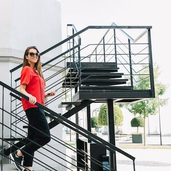 Vista laterale di una donna alla moda che si muove giù per le scale