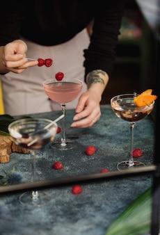 Vista laterale di una donna che decora un cocktail rosa con frutti di bosco