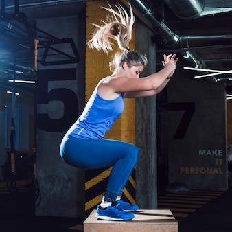 Vista laterale di una donna che fa allenamento in palestra
