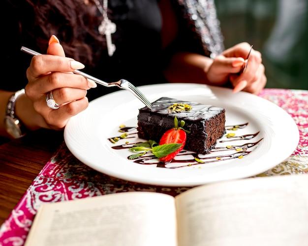 Vista laterale di una donna che mangia la torta di cioccolato decorata con la fragola alla tabella