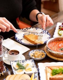 Vista laterale di una donna che mangia pane tostato con miele al tavolo