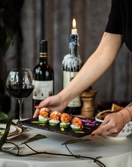 Vista laterale di una donna che mette una tavola con gamberi fritti su avocado alla griglia condita con salsa di panna