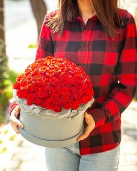 Vista laterale di una donna che tiene una composizione di rose di colore rosso in scatola