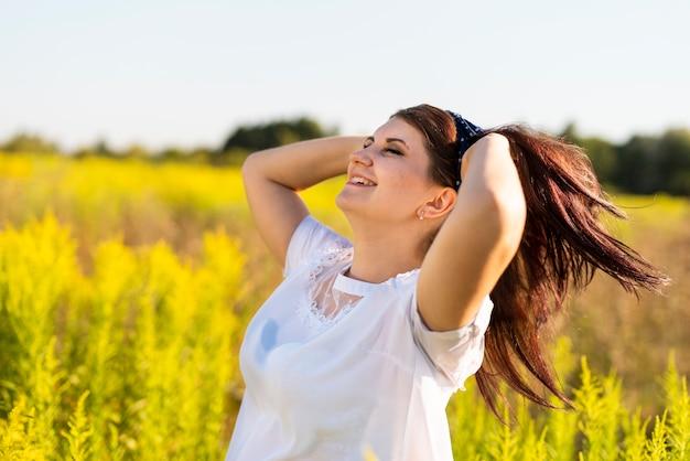 Vista laterale di una donna con la mano tra i capelli