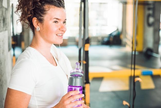 Vista laterale di una donna felice che tiene la bottiglia d'acqua
