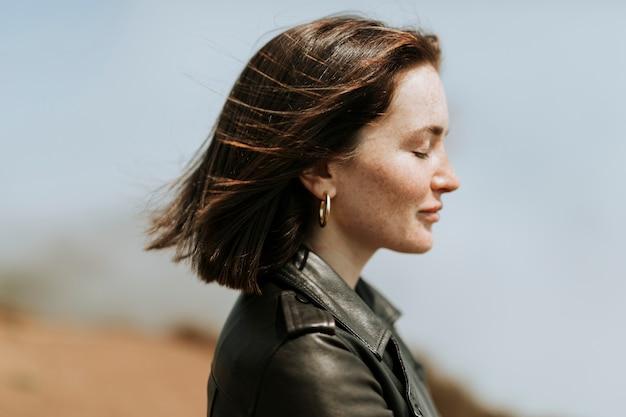 Vista laterale di una donna in giacca di pelle in piedi in un parco
