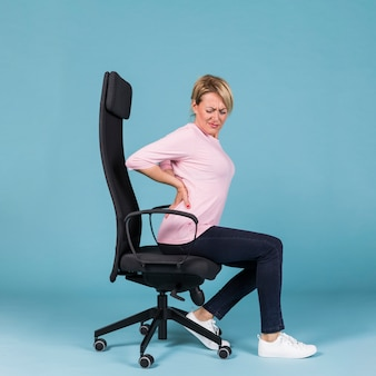 Vista laterale di una donna seduta in poltrona soffre di mal di schiena