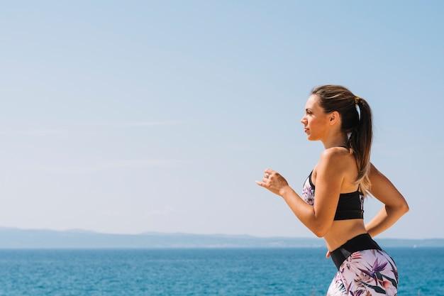 Vista laterale di una femmina in abiti sportivi in esecuzione vicino al mare