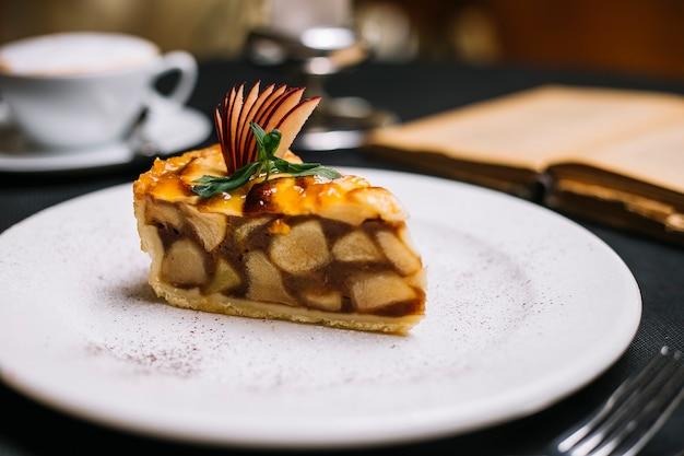 Vista laterale di una fetta di torta di mele su un piatto bianco
