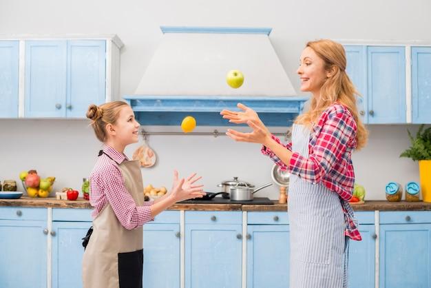 Vista laterale di una figlia e sua madre gettando mela e limone in aria in cucina