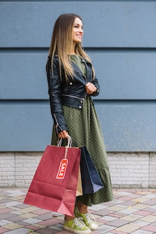 Vista laterale di una giovane donna alla moda che indossa giacca tenendo i sacchetti di shopping in mano