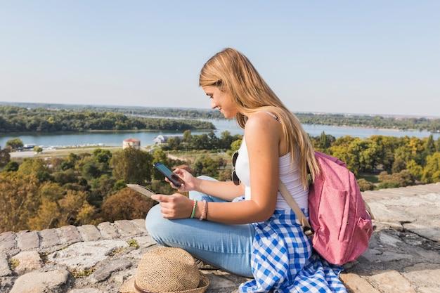 Vista laterale di una giovane donna alla ricerca di direzione nel telefono cellulare