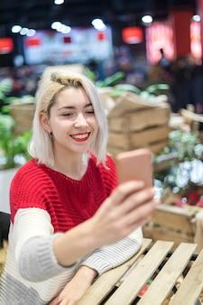 Vista laterale di una giovane donna bellissima prendendo un selfie in un bar.