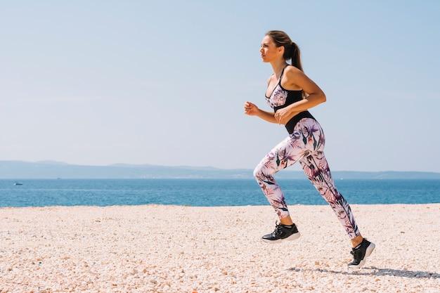 Vista laterale di una giovane donna che corre sulla spiaggia