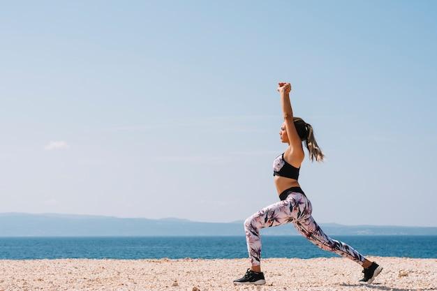 Vista laterale di una giovane donna che fa esercizio di stretching vicino alla spiaggia