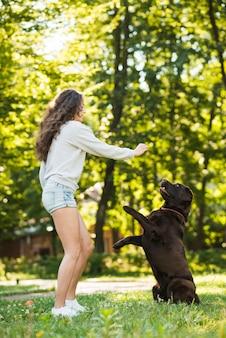 Vista laterale di una giovane donna che si diverte con il suo cane in giardino